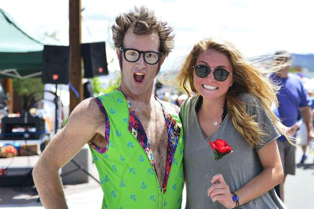 "Performing as the character ""Adorkable Derek,"" street performer Derek McAlister poses for a photo with Maya McDaniel, whom McAlister pulled from the audience to serve as Adorkable Derek's love interest, after a Saturday performance at the Frisco BBQ Challenge."