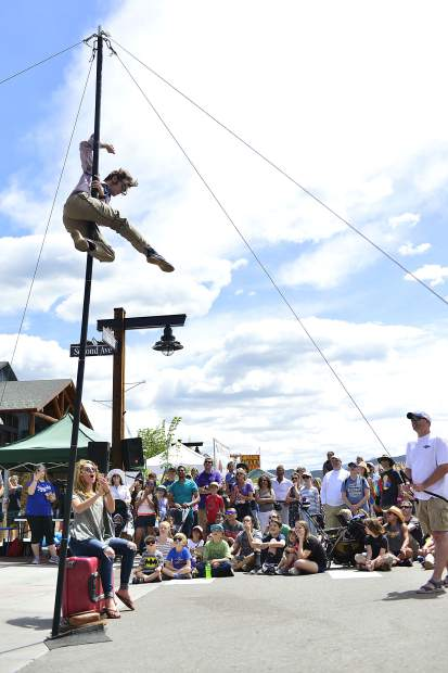 Street performer Derek McAlister of Los Angeles performs stunts atop an 18-foot pole Saturday during the 24th Frisco BBQ Challenge. At the base is Maya McDaniel of Columbus, Ohio, who got more than she bargained for when she stopped to watch the show and became a part of it.