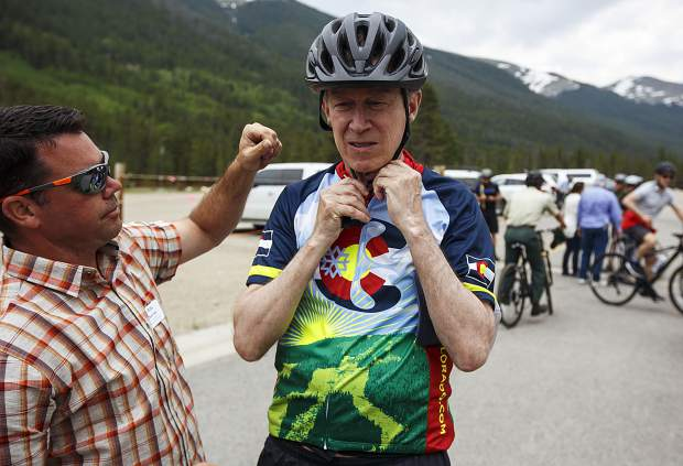 Gov. John Hickenlooper puts on a bike helmet ahead of a bike ride with a group towards Frisco from Copper Mountain Thursday, June 22.
