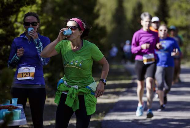 Run the Rockies participants rehydrate along the recreation path during the 10K race between Copper Mountain and Frisco Saturday, June 3, 2017.