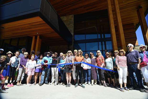 """A large group of people who attended Saturday's ribbon-cutting ceremony for the new $9 million Silverthorne Performing Arts Center come together for one last chop at the ribbon. Before the ribbon-cutting, Silverthorne Mayor Bruce Butler applauded the """"community spirit"""" and many partnerships that helped the new facility come to fruition."""