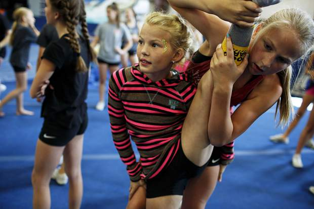 Woodward cheerleading campers stretch ahead of a full-session Wednesday, June 28, at Copper Mountain.
