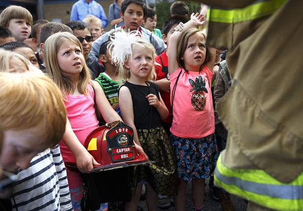 Dillon Valley Elementary School students listen to Lake Dillon Fire-Rescue Capt. Jason Bell's demonstration of suiting up in a fire suit during an event at the school grounds Wednesday, May 31, 2017, in Dillon. The local law enforcement and fire departments were visiting a community event, in which the Elements Church were giving away 400 pairs of brand-new slip-on shoes to students as a way to give back to the community.