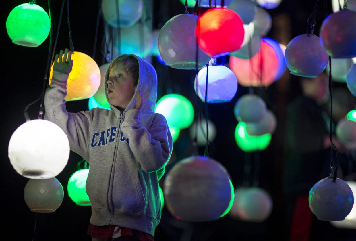 A young visitor interacts with suspended globes during BreckCreate's WAVE festival at the Blue River Plaza Thursday June 1, 2017, in downtown Breckenridge.