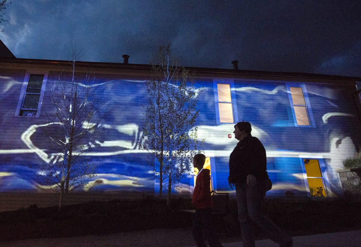 Pedestrians walk past the moving digital projection against the Old Masonic Hall exterior wall, an art piece by Andrew Wade Smith of Portland, Oregon, along Washington Ave. during BreckCreate's WAVE art festival June 2, 2017, in Breckenridge.