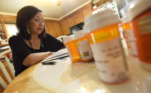 Sandi Elder flips through her kidney transplant handbook as she's surrounded by a variety of medicines she has to take while at her home in Greeley.