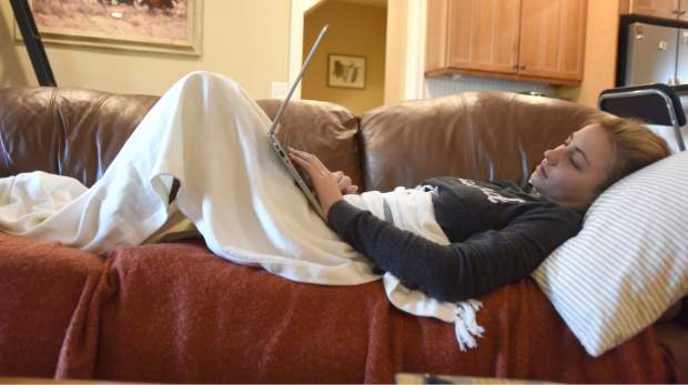 Layne Pachl rests on the couch at her home as pain killers begin to work a few days after her surgery.