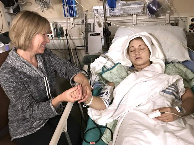 Layne Pachl rests after the transplant is complete while her mother, Tamara, holds her hand May 31 at University of Colorado Hospital in Aurora.