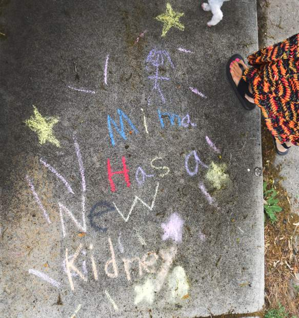 Sandi Elder passes by a chalk message left by her grandchildren.