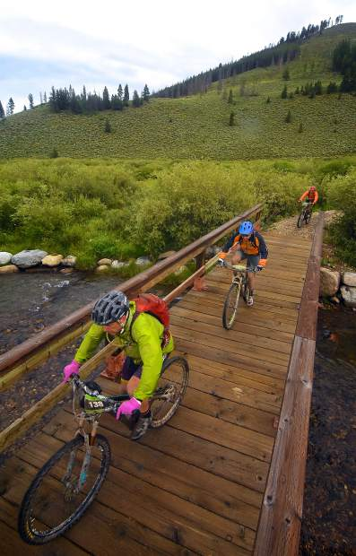 A train of riders crosses the bridge near Tiger Dredge after finishing the Colorado Trail portion of the Breck 100 on July 29. The event drew nearly 300 riders from across the world for 32, 68 and 100 mioles of riding in constant rain and chilly temperatures.
