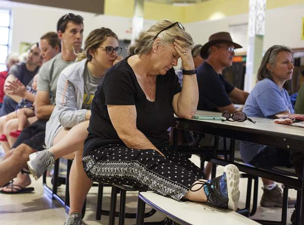 Nebraska resident, Sheila Calhoun, who evacuated her rental home due to Peak 2 fire, rests her head during a briefing inside Summit Middle School lobby Wednesday, July 5 in Frisco.