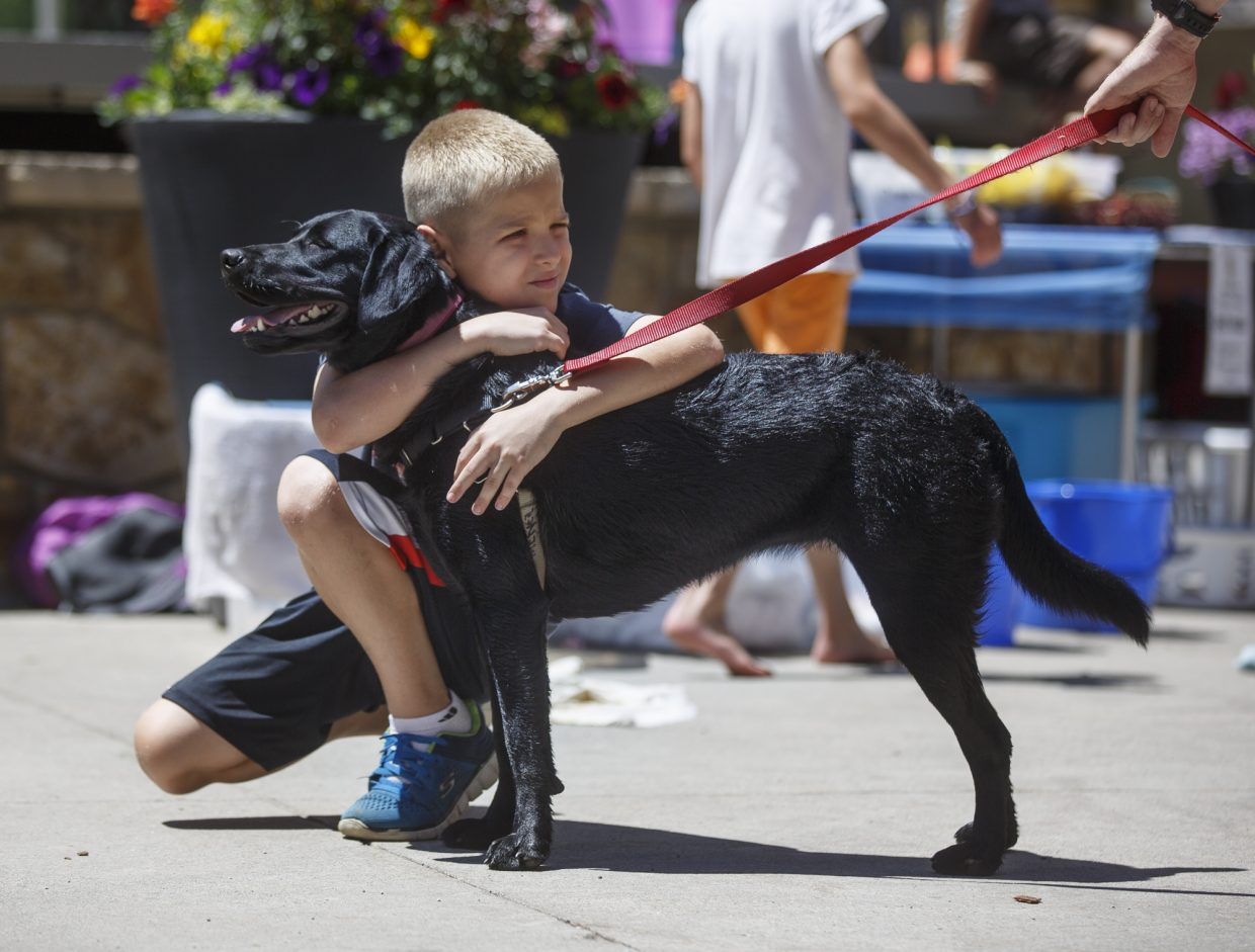 Morgan Potts, 10, of Austin, Texas, hugs Buttercup following his black lab's bath by the Mountain Top Camp students during a fundraiser Wednesday, July 19, at the Main Street Station in Breckenridge. The 9th annual dog wash were raising funds for the non-profit Mountain Top Children's Museum.