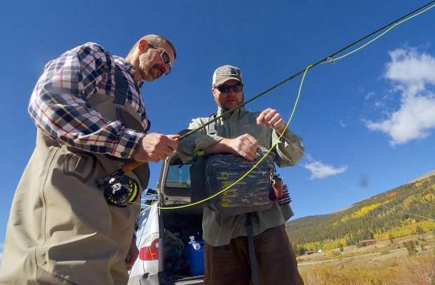 Fly-fishing guide Justin Wyman (right) with Breckenridge Outfitters shows client Jon Ventura of Los Alamos, New Mexico how to tie a fly to a tippet before casting in Alma. Wildflowers are in season for mid-July, as are hopper rigs.