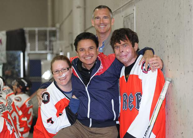 Flight For Life helicopter crash survivor Dave Repsher, right, poses for a photo during the Dawg Nation Foundation's annual Dawg Bowl weekend fundraiser at Edge Ice Arena in Littleton, Colorado. Joining him, from left to right: Christina Montoya, Dawg Nation president Martin Richardson and former Colorado Avalanche player Pierre Turgeon.