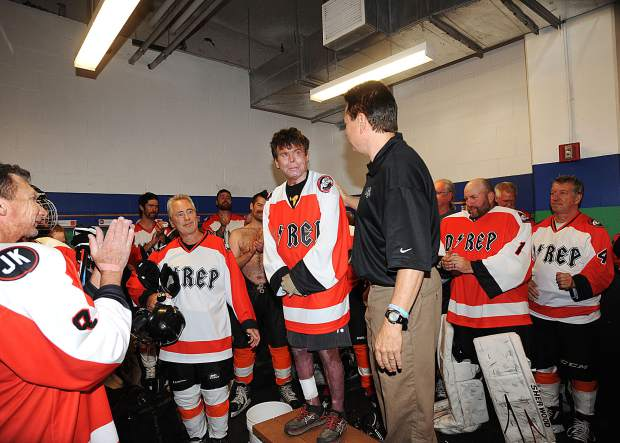 Dave Repsher, center, gave a locker room speech to participants before the Dawg Nation Hockey Foundation's annual Survivor Game in Littleton, Colorado, the last weekend of June. Both teams wore sweaters bearing Repsher's nickname D-Rep in honor of the critically injured Flight For Life flight nurse.