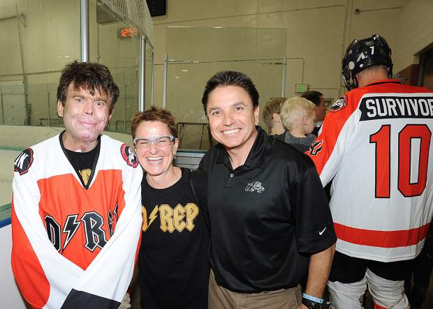 Flight For Life helicopter crash survivor Dave Repsher, left, took a few moments to pose for a photo with his wife, Amanda, center, and, right, Dawg Nation Hockey Foundation president Martin Richardson. Repsher was the guest of honor for the nonprofit's annual Dawg Bowl weekend fundraiser at Edge Ice Arena in Littleton, Colorado.
