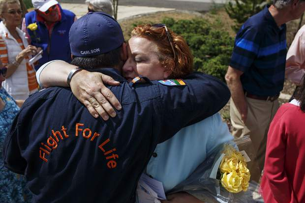 Karen Mahany receives an embrace Monday morning from a member of the Flight For Life crew during a prayer service at the memorial in Frisco dedicated to her husband. Patrick Mahany, 64, was the pilot of the Lifeguard 2 helcopter that crashed near St. Anthony Summit Medical Center on July 3, 2015.