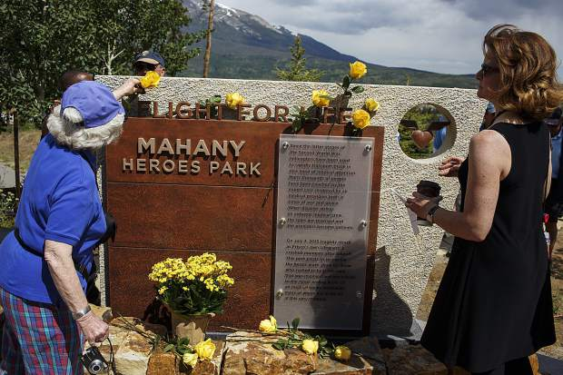 Prayer service attendees place yellow roses in honor of the victims of the Flight For Life helicopter crash two years ago at a memorial known as Mahany Heroes Park in Frisco on Monday, July 3.
