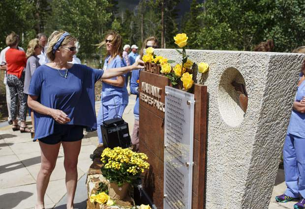 A prayer service attendee places a yellow rose in honor of the victims of the Flight For Life helicopter crash two years ago at a memorial known as Mahany Heroes Park in Frisco on Monday, July 3.