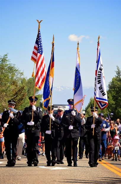 The Red, White and Blue Fire District colorguard carries the American and Colorado flags onto Main Street for the start of the Breckenridge Fourth of July parade.