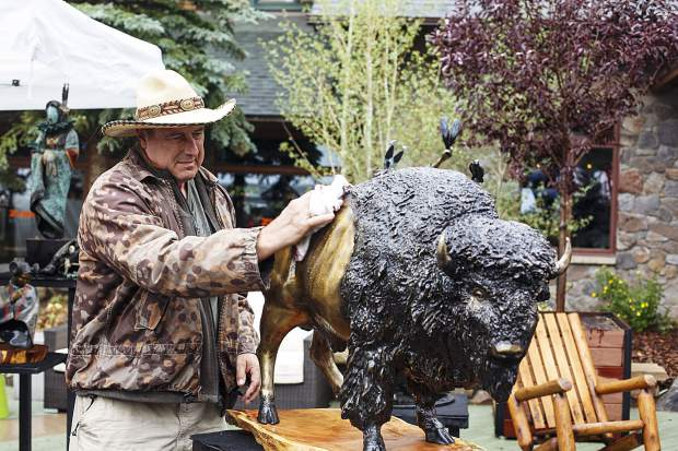 Artist Steven Schneider dries off his bronze sculpture piece of a buffalo during the Keystone's River Run Village Art Festival Saturday, July 29, at Keystone Ski Resort.