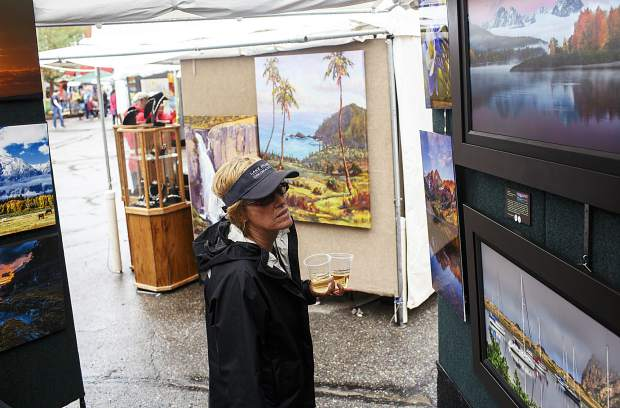 A visitor checks out photos by Randy Koepsell during the Keystone's River Run Village Art Festival Saturday, July 29, at Keystone Ski Resort.