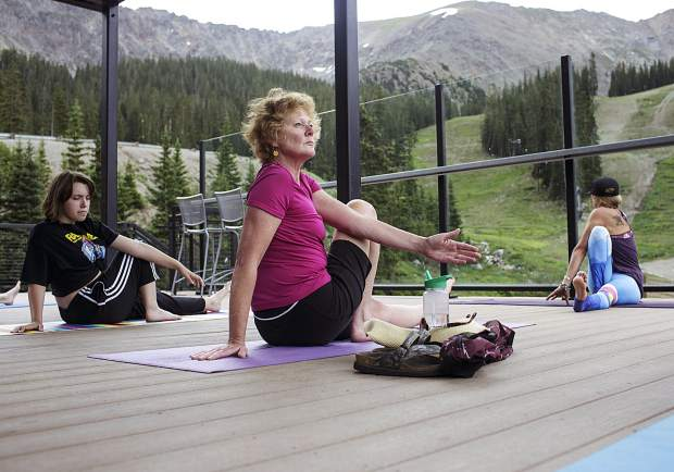 Nancy Bergen, center, and other Summit County residents participate in a yoga session Friday, July 21, at Arapahoe Basin Ski Area. The resort is in its first year offering yoga on Friday mornings to constumers, which lasts until August 18.