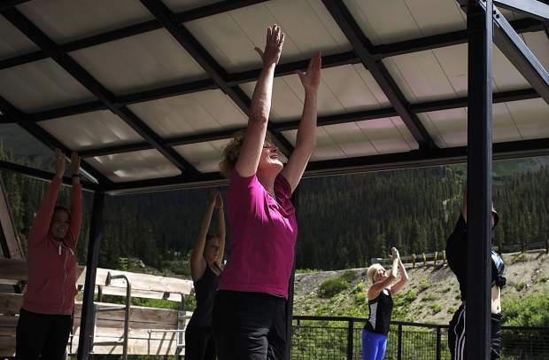 Nancy Bergen, center, and other Summit County residents participate in a yoga session Friday, July 21, at Arapahoe Basin Ski Area.