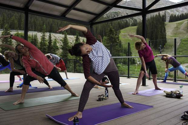 Ashley Ojala, center, and other Summit County residents participate in a yoga session Friday, July 21, at Arapahoe Basin Ski Area.