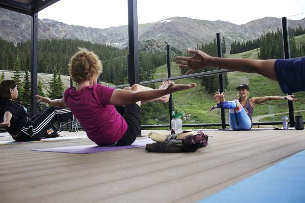 Local instructor Sarah Schwartz, in background, leads a yoga pose for the participating group during a session Friday, July 21, at Arapahoe Basin Ski Area.