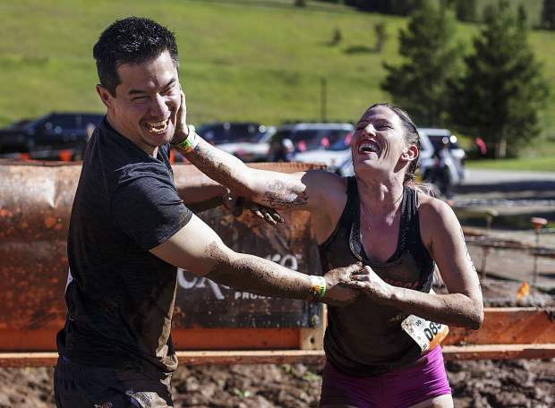 Competitors Shoshana Frost, right, and Nathan Long, both of Denver, attempt to spread mud on each other during the 12-mile Tough Mudder obstacle course Saturday, July 15, at Copper Mountain.