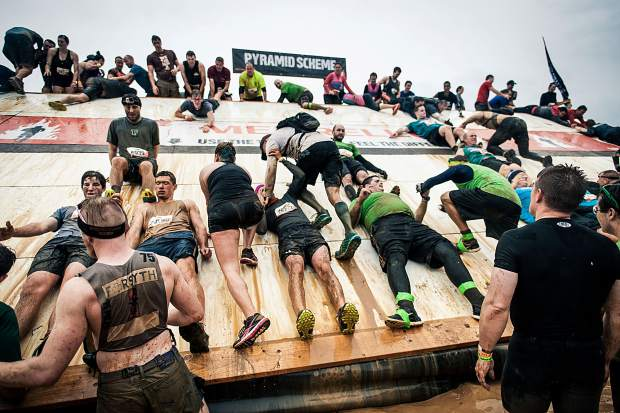 Teams and strangers work together to scamper up and over the slippery surface of Pyramid Scheme at a Past Tough Mudder. For summer 2017, the obstacle race series makes its Copper Mountain debut from July 15-16 with two days of mud pits and electrical shocks.
