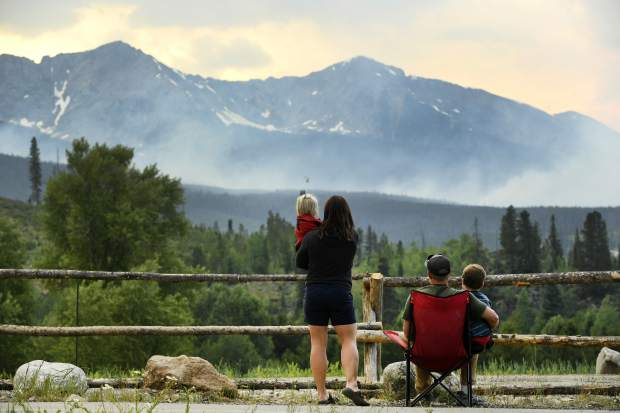 Amy Noraka, holding daughter Sage, 3, left, and her husband Chris Noraka, with son Tyler, 6, watch as helicopters dump water on a wildfire near the Peak 2 in Breckenridge, Colo., Thursday, July 6, 2017. Firefighters were working Thursday to keep the wildfire that's forced the evacuation of hundreds of people from spreading toward homes near Colorado's Breckenridge Ski Resort and the nearby historic town. (Helen H. Richardson/The Denver Post via AP)