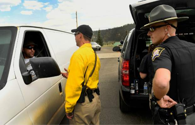 Summit County Sheriff's deputies SJ Hamit, middle, and Mike Schilling, talk to residents about access to the Peak 7 neighborhood in Breckenridge, Colo., Thursday, July 6, 2017. Firefighters were working Thursday to keep a wildfire that's forced the evacuation of hundreds of people from spreading toward homes near Colorado's Breckenridge Ski Resort and the nearby historic town. (Helen H. Richardson/The Denver Post via AP)