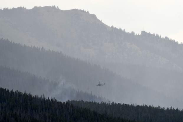 A helicopter makes water drops on a wildfire near the Peak 2 as it continues to burn in the White River National Forest between Breckenridge and Frisco, Colo., Thursday, July 6, 2017. Firefighters were working Thursday to keep the wildfire that's forced the evacuation of hundreds of people from spreading toward homes near Colorado's Breckenridge Ski Resort and the nearby historic town. (Helen H. Richardson/The Denver Post via AP)