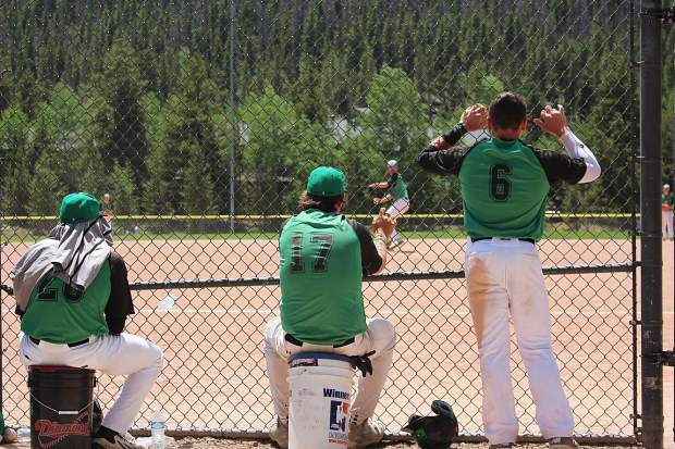 Three Summit Extreme Black Diamonds watch on as a new pitcher warms up for the team in the first game of a doubleheader against the Steamboat Storm on the Fourth of July.