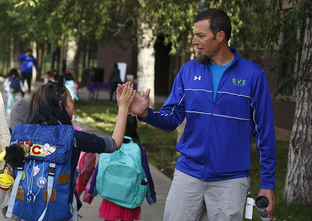 Silverthorne Elementary physical education teacher Tyler Bunnelle, right, high-fives student Kyah Quam as she arrives for first day of school Thursday, Aug. 24, in Silverthorne.