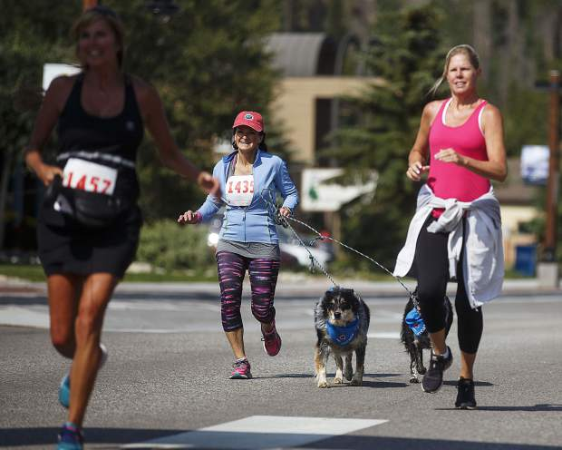 Canine 4K participants jog the last stretch of the race on Frisco's Main Street Saturday.