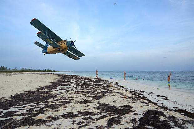 A crop duster prop plane flies low on the Cuban island of Cayo Largo del Sur in late-May while a large group of American citizens took up brief residence on the beach resort.