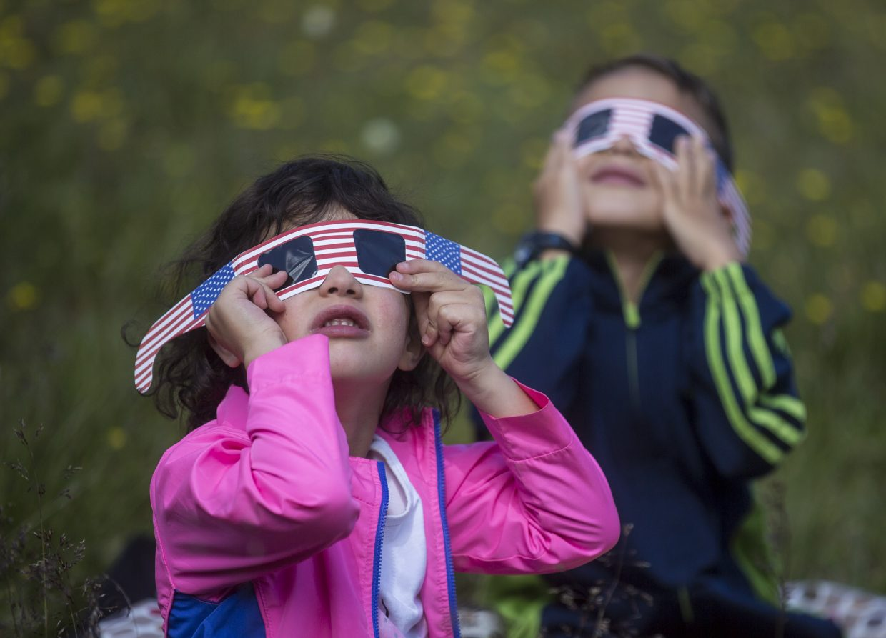 Alice Prostak, 5, and her brother Sam, 7, in background view the solar eclipse through the goggles Monday, Aug. 21, at Arapahoe Basin.