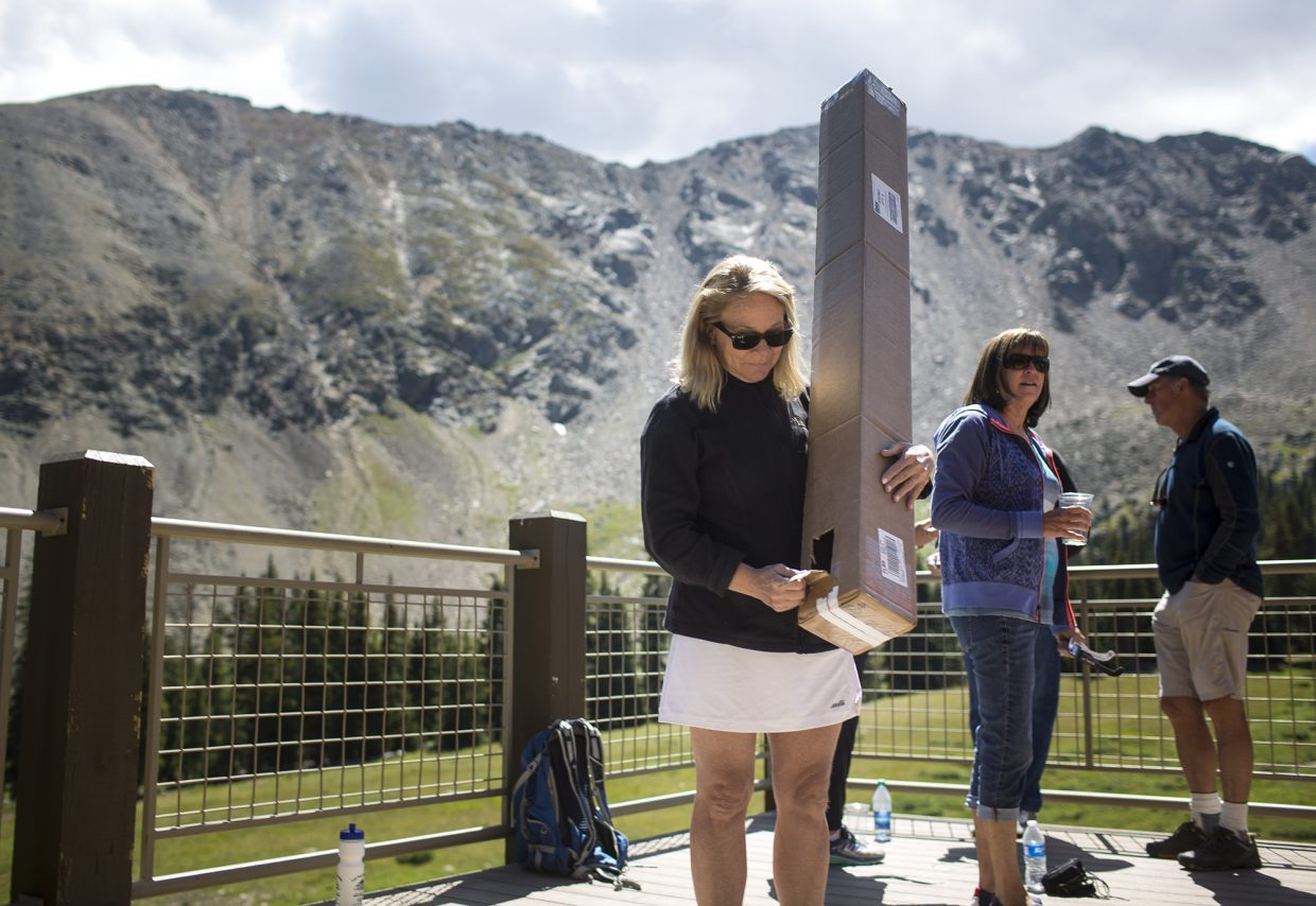 Elyse Degroot views the solar eclipse from the homemade pinhole projector box made with a cardboard, aluminum foil, and tape Monday, Aug. 21, at Arapahoe Basin.