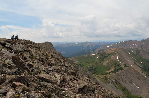 Fellow hikers sit on the summit of Buffalo Mountain. Below them, the ridgeline that Eccles Pass crosses over. These ridges are part of the Gore Range.