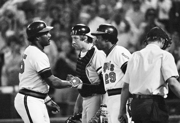 FILE - In this Oct. 5, 1979, file photo, California Angels' Don Baylor, left, gets a handshake from teammate Rod Carew (29) after hitting a home run in the fourth inning of Game 3 of the American League playoffs against the Baltimore Orioles, in Anaheim, Calif. Baltimore catcher Dave Skaggs is at center. Don Baylor, the 1979 AL MVP with the California Angels who went on to become manager of the year with the Colorado Rockies in 1995, has died. He was 68. Baylor died Monday, Aug. 7, 2017, at a hospital in Austin, Texas, his son, Don Baylor Jr., told the Austin American-Statesman. (AP Photo/File)