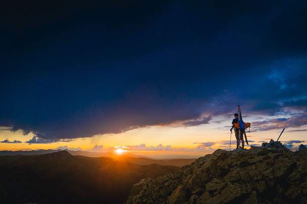 In search of skiing on snow in August, skier Travis Halverson overlooks the sun above the horizon.