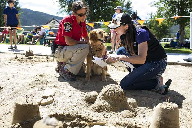 Recco, an avalanche dog for Summit County Rescue Group, judges the sandcastle building and design with Lake Dillon Ranger Erin Sirek, left, and Jenn Shimp making notes of results for the seventh annual kids sandcastle competition at the Frisco Marina, Saturday, in Frisco.