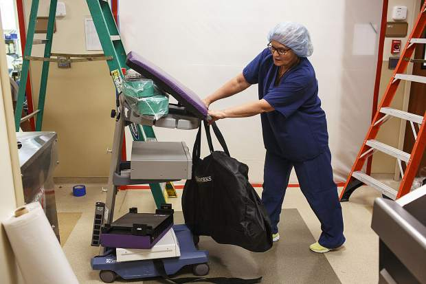 Peak One Surgery Center's Director of Ambulatory Surgery Alena Pochman moves medical equipment to a room due to restoration projects in other areas of the hospital Wednesday, Aug. 9, in Frisco, due to the flooding that occurred on Tuesday evening.