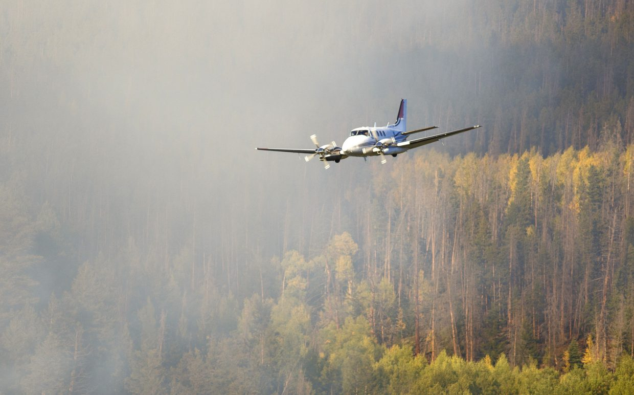 A spotter aircraft flies by the Tenderfoot2 Fire Monday, Sept. 18, in Dillon.