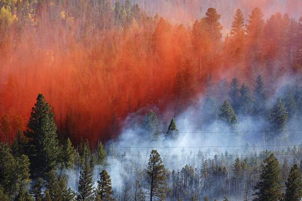 Fire retardant slurry dumped by an air tanker spreads onto Tenderfoot2 Fire Tuesday, Sept. 19, in Dillon.