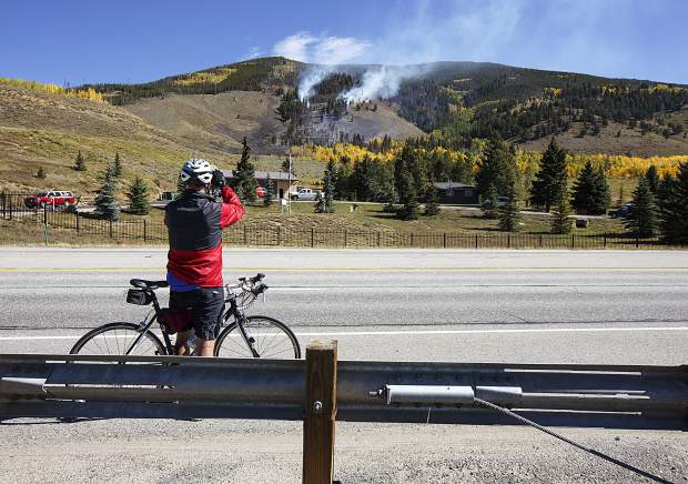 A passing cyclists stops to take photos along Highway 6 of the Tenderfoot2 Fire Tuesday, Sept. 19, in Dillon.