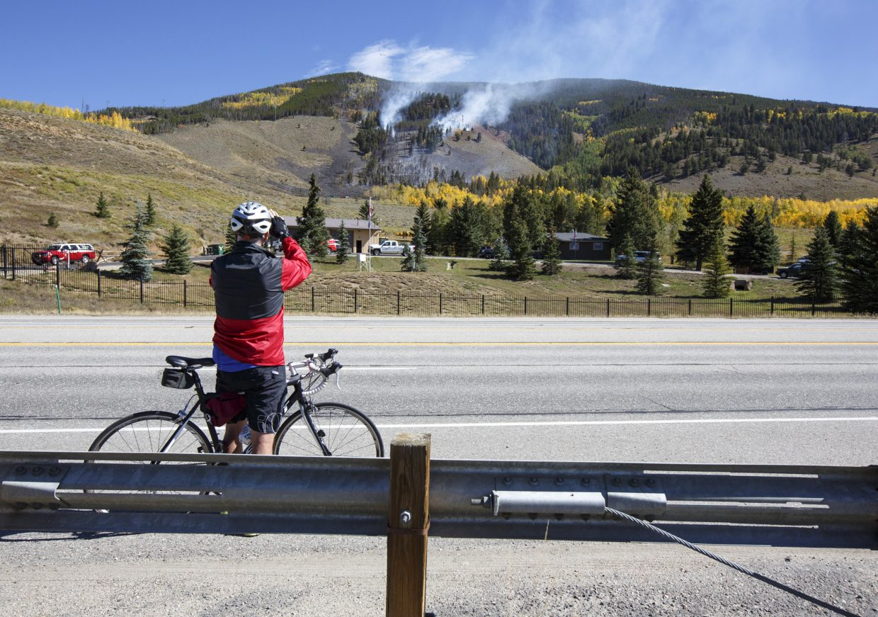 A passing cyclists stops to take photos along Highway 6 of the Tenderfoot 2 Fire Tuesday, Sept. 19, in Dillon.
